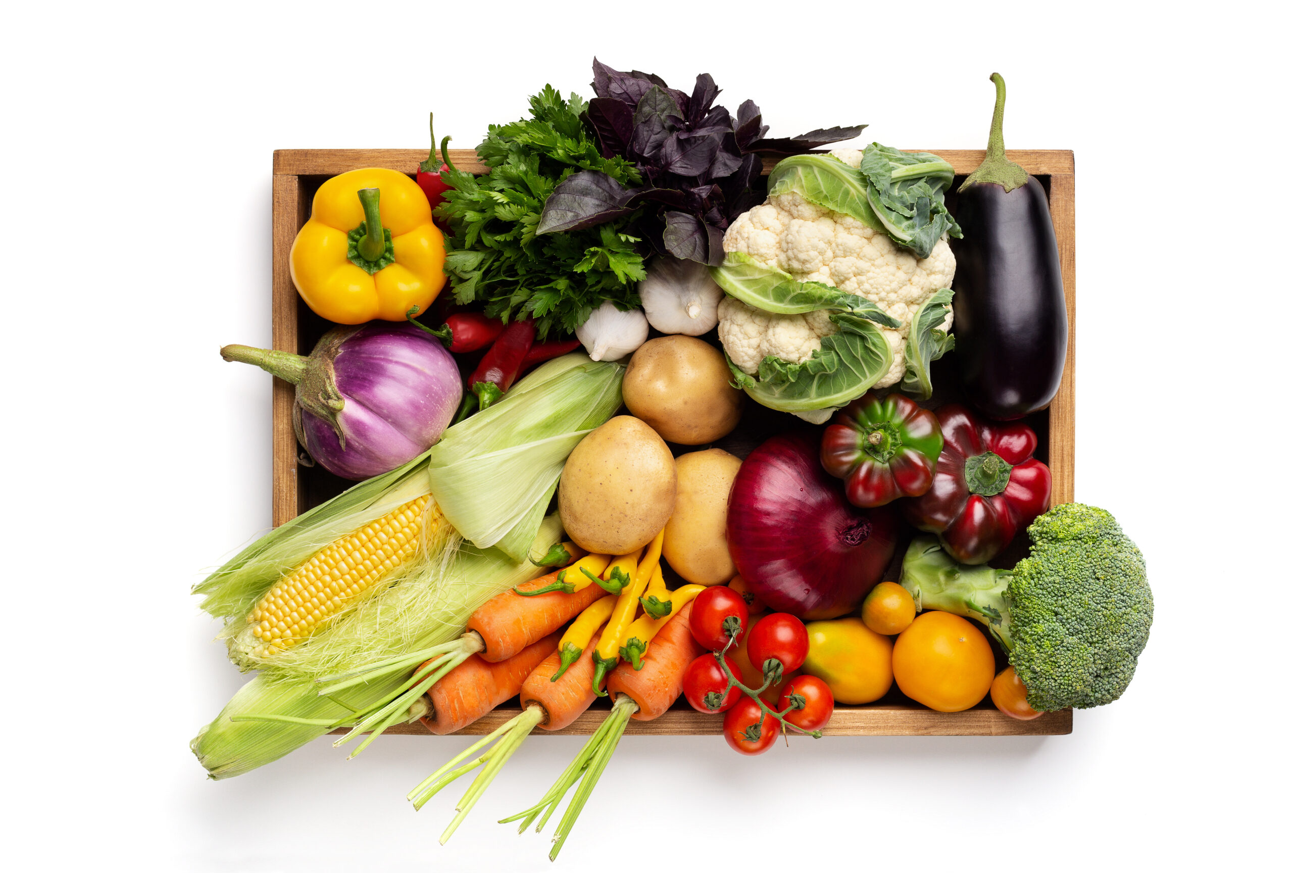 Healthy organic food. Fresh vegetables assortment in wooden box on white background, top view